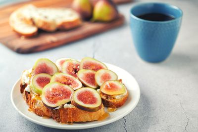 Toast with ricotta cheese, sliced figs, and honey on a plate