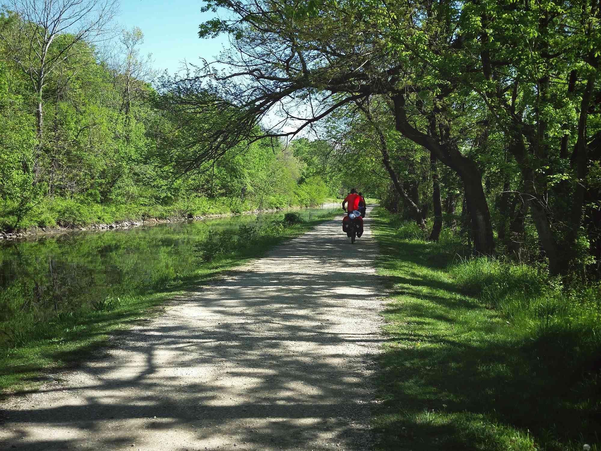 Cyclists ride down a gravel pathway next to a canal in a forest