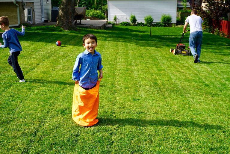 child plays on freshly mowed lawn