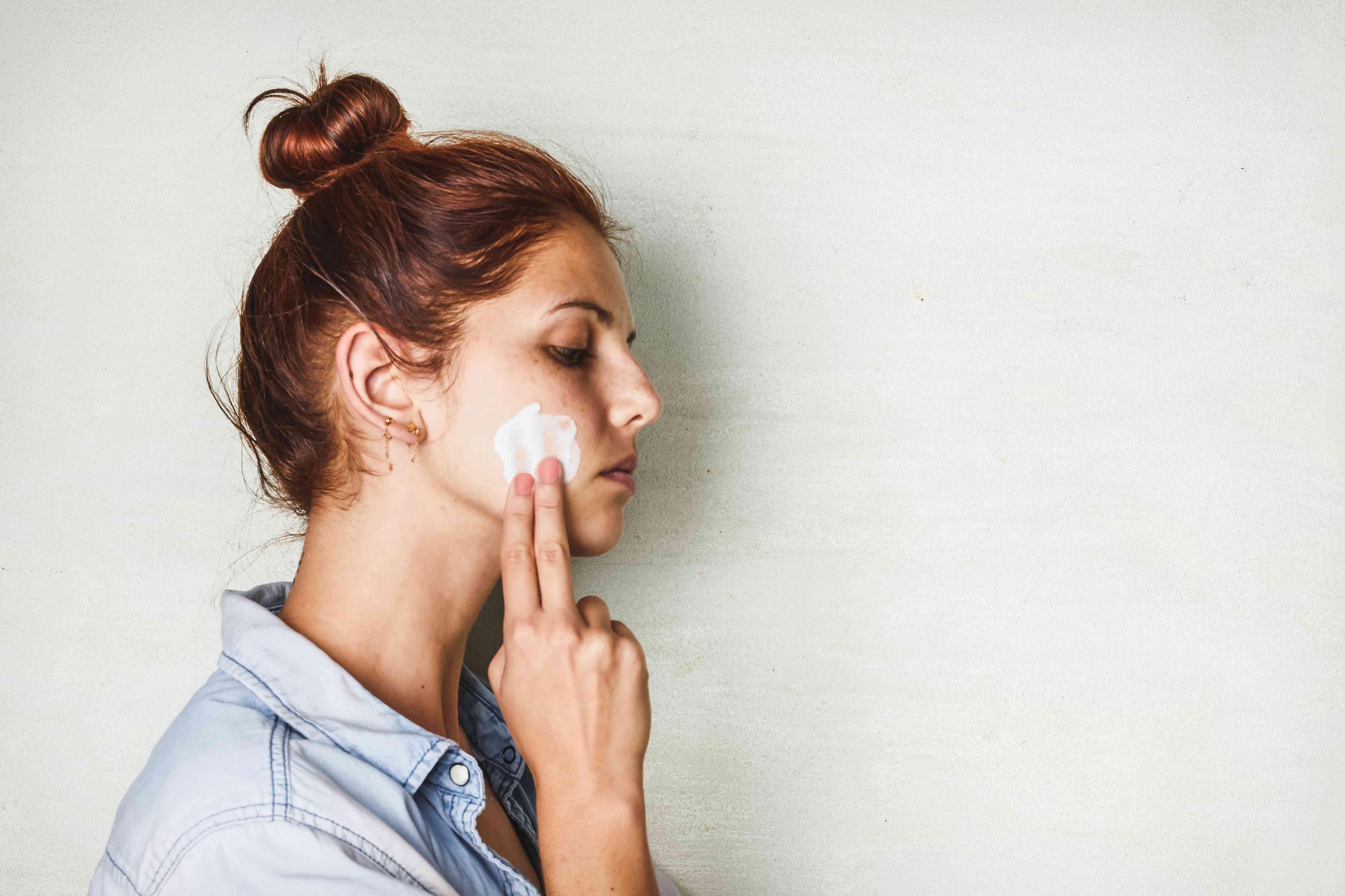 woman with top bun rubs plain Greek yogurt on her face to clean skin