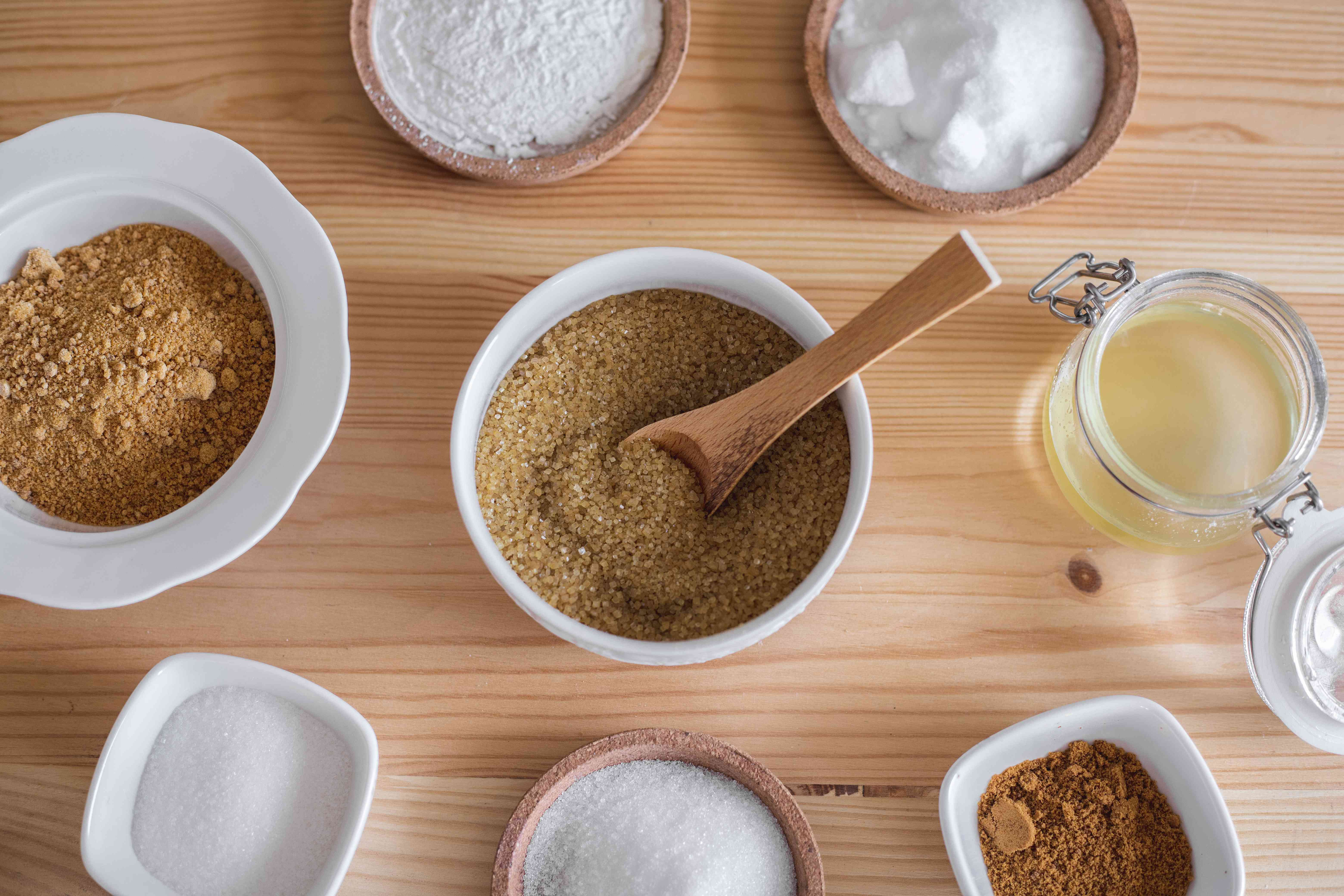 overhead shots of different types of brown and white sugars in bowls on wooden table