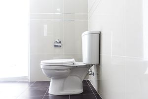 Side view of a white toilet in a white tile bathroom