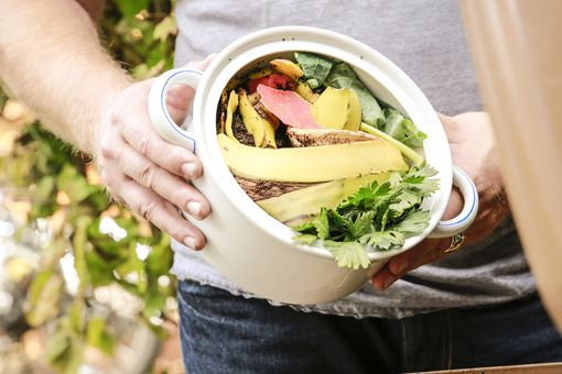 Mature man throwing kitchen scraps into bio-waste container