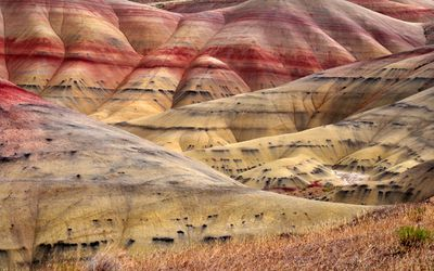 A hilly landscape with stripes of red, yellow, and black