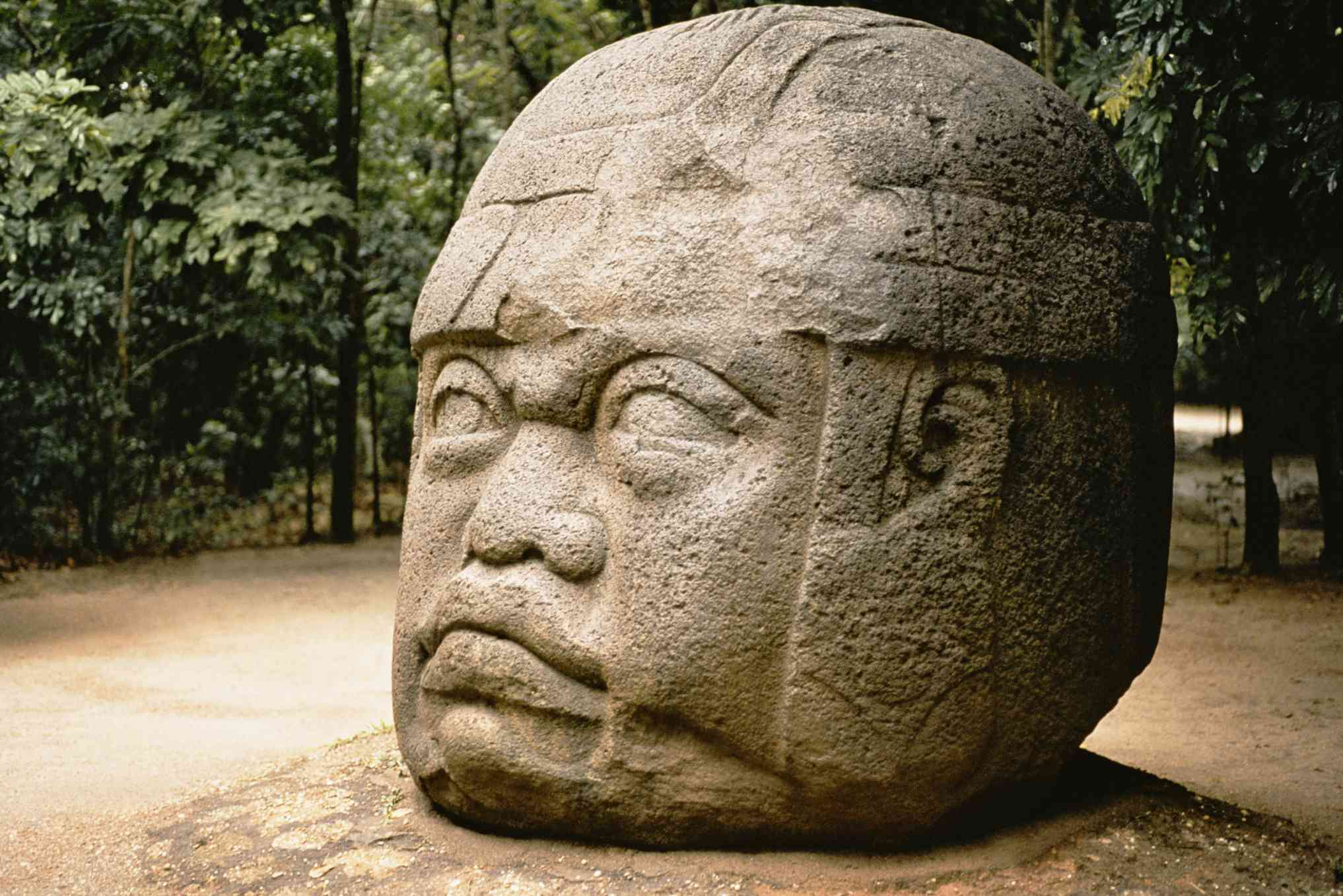 Colossal stone head protruding from ground in Mexico