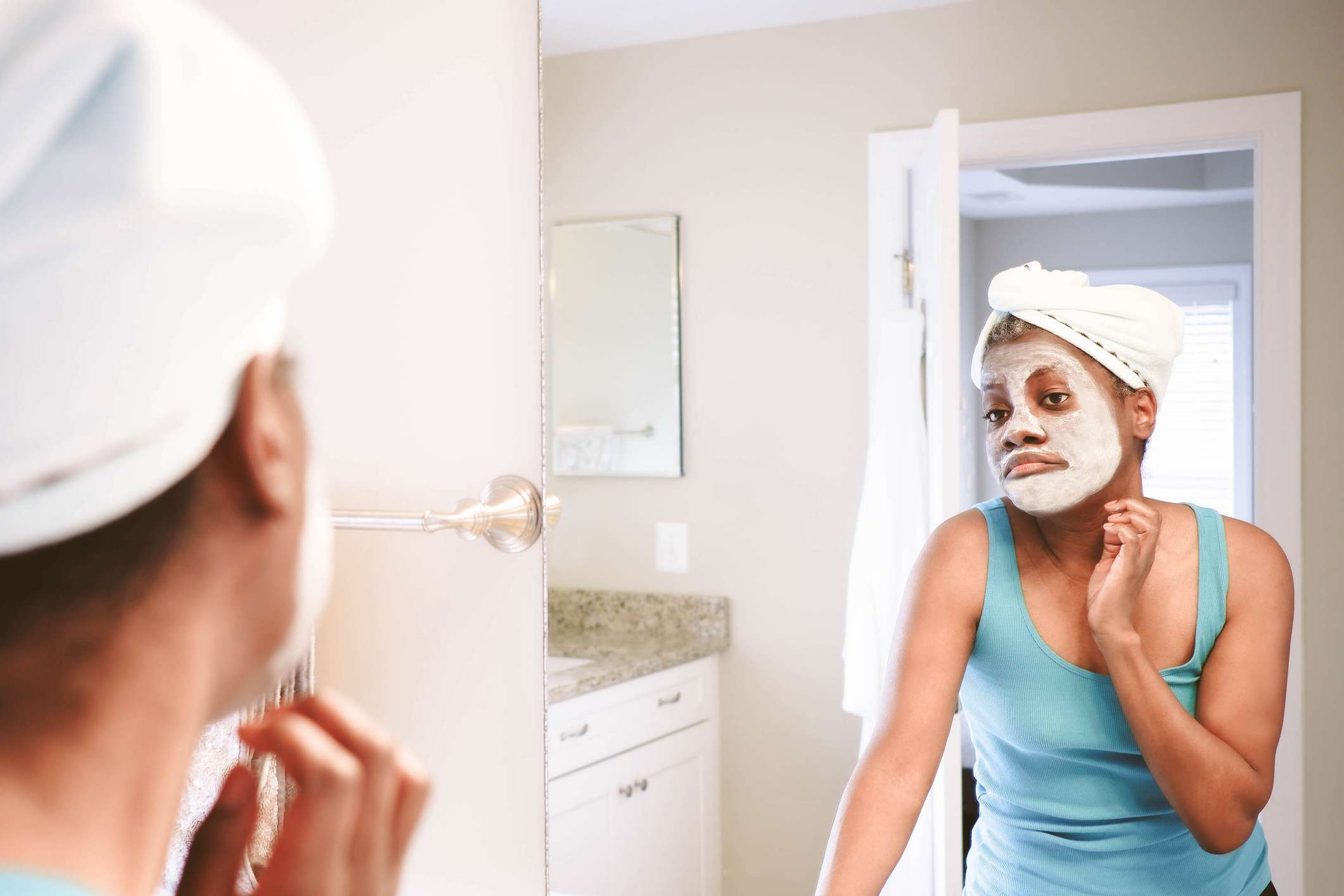 A black woman with clay facial mask looks at herself in the mirror.