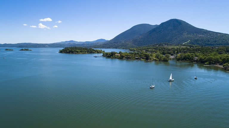 The aerial low-altitude scenic view of the Buckingham Park on the Clear Lake, California, with yachts on a moorage. The sunny spring day.