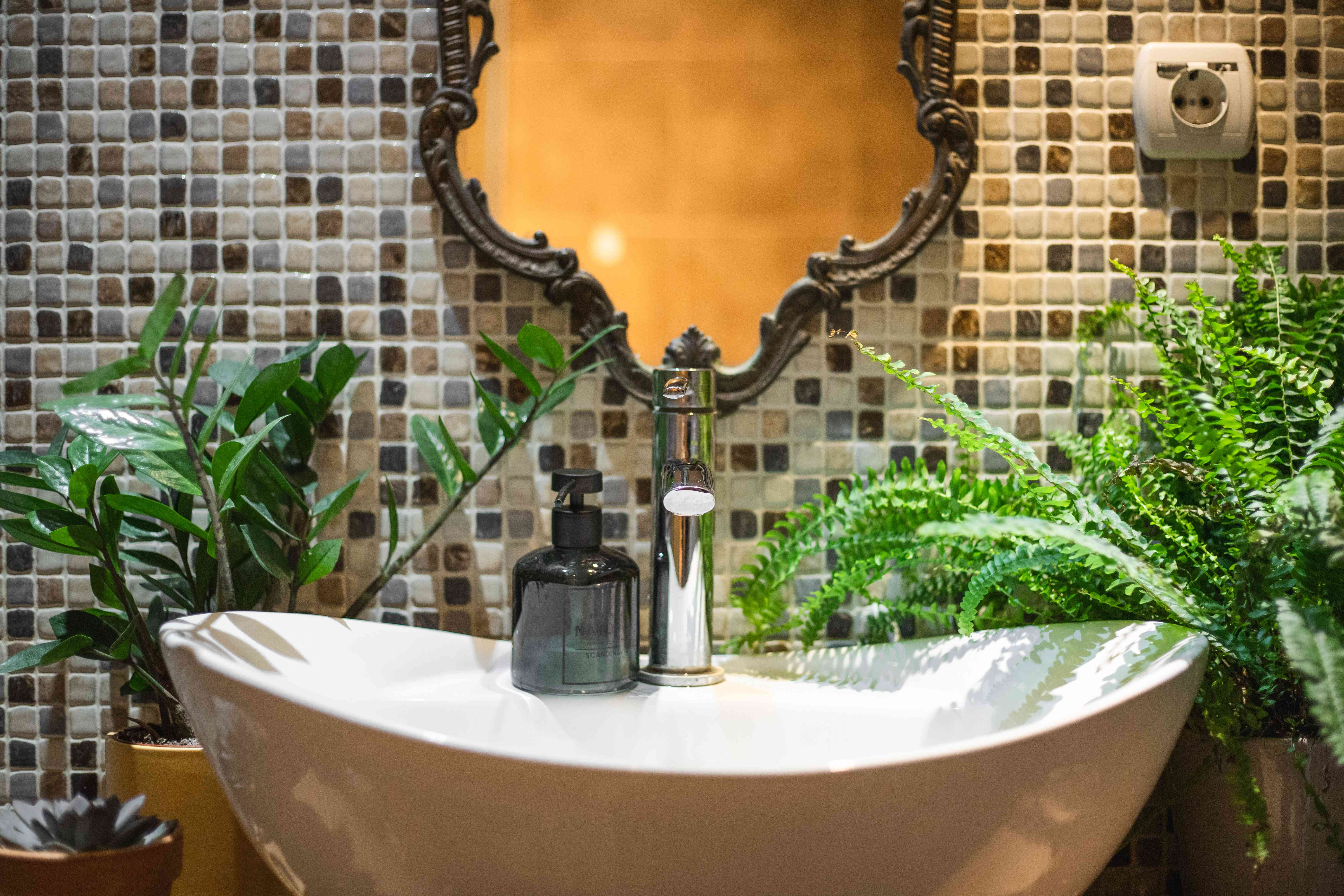 large scooped bathroom sink with tiled wall surrounded by ferns and other house plants