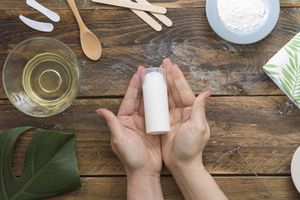 Hands holding DIY beauty product surrounded by natural ingredients