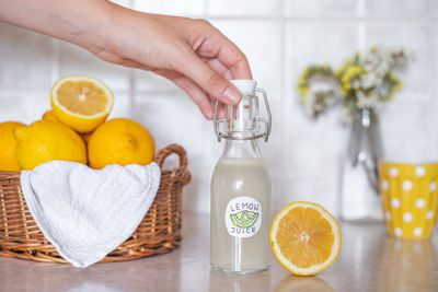 hand reaches for fresh-squeezed lemon juice next to cut lemon and woven basket of lemons
