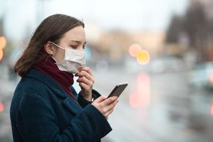 Young girl wearing a protective face mask and checking air pollution with smartphone