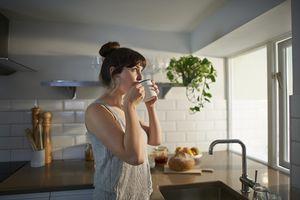 Woman drinking from mug in zero waste kitchen