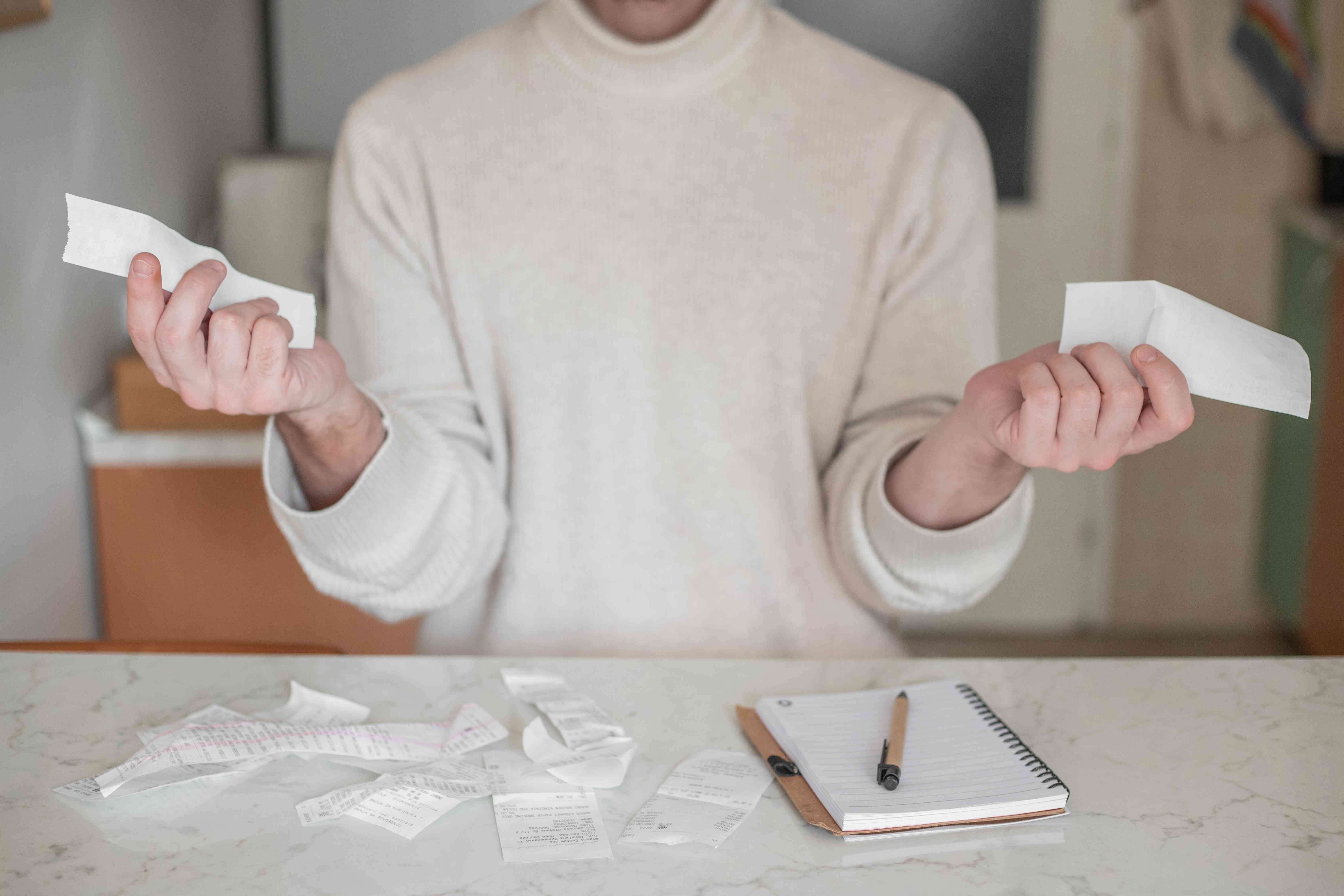 person in cream sweater holds different paper receipts in each hand