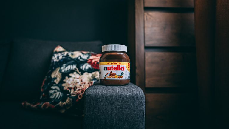 Jar of Nutella on the arm of a couch