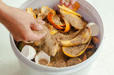 A young person is composting kitchen scraps in a plastic container