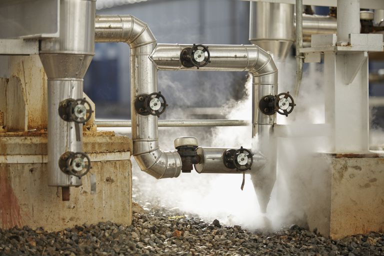 steam being released from pipes in an industrial setting