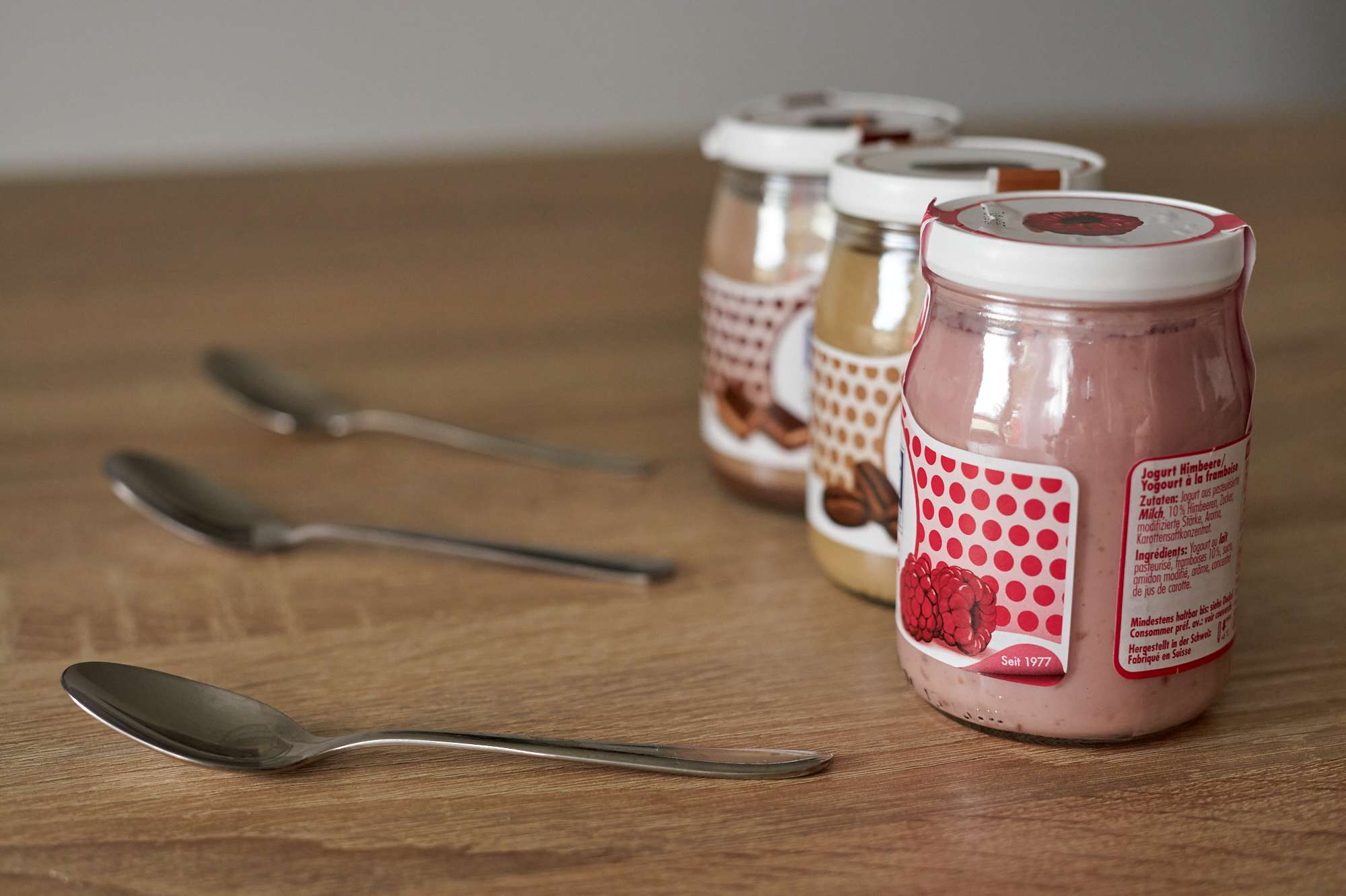 three glass jars of yogurt with three spoons on wooden table