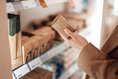 A woman looks at recyclable packaging on cosmetics in a store.