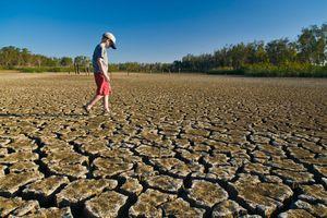 boy walking on cracked dry earth