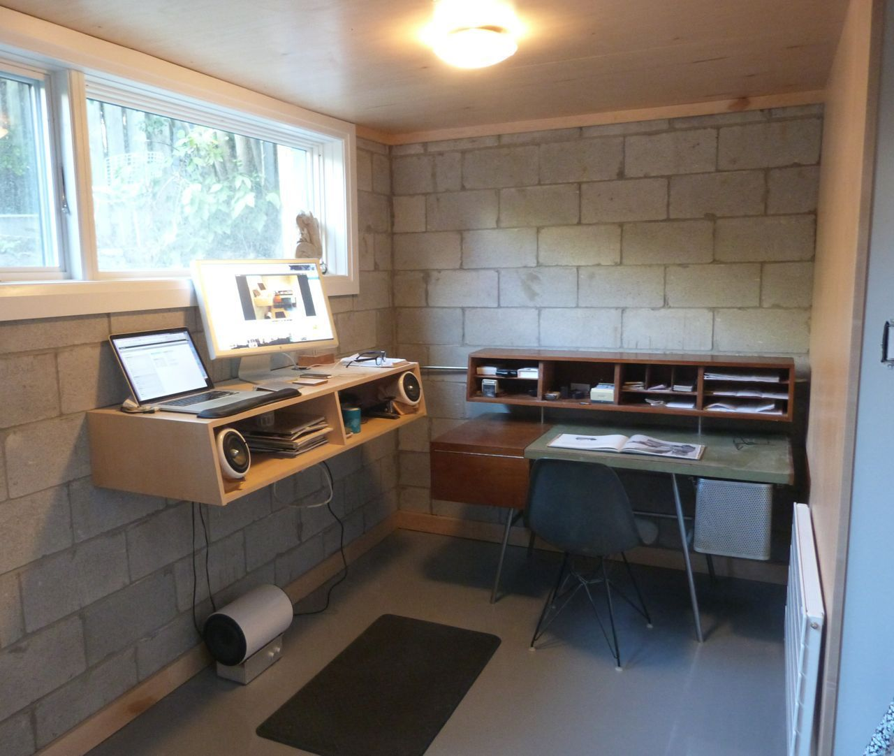 An office setup with a desk and storage in a small cinder block walled room
