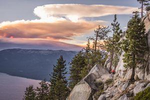 A woman mountain biking along a rocky trail above Lake Tahoe