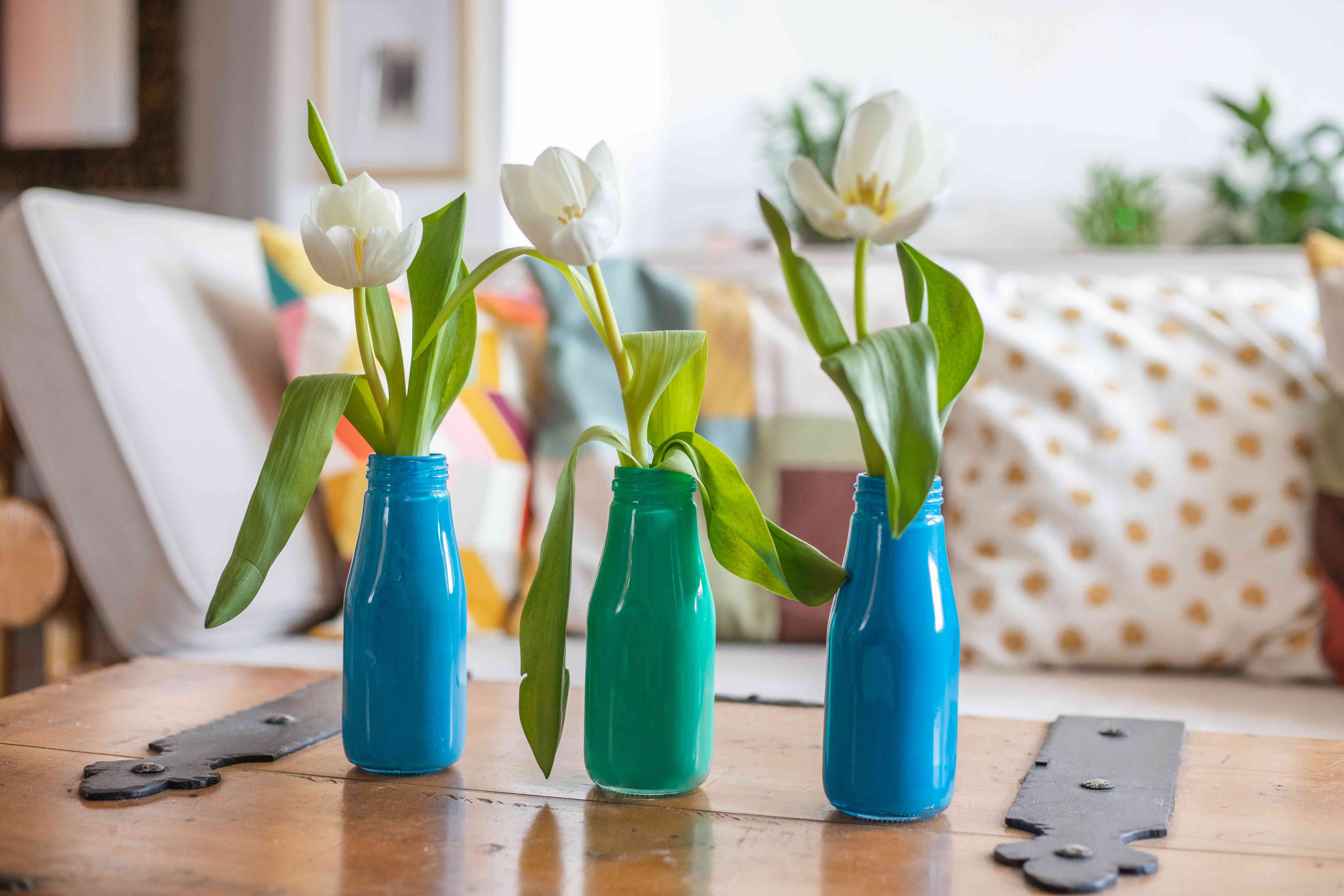 glass bottles upcycled into painted bud vases holding white tulips on wooden table