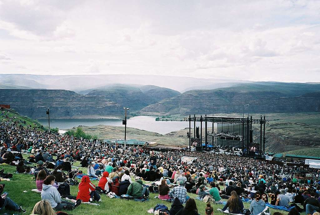 view of crowd sitting on grassy hill facing Gorge Amphitheatre below with Columbia River and mountains in background