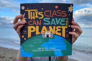 Hands holding a colorful book titled This Class Can Save the Planet