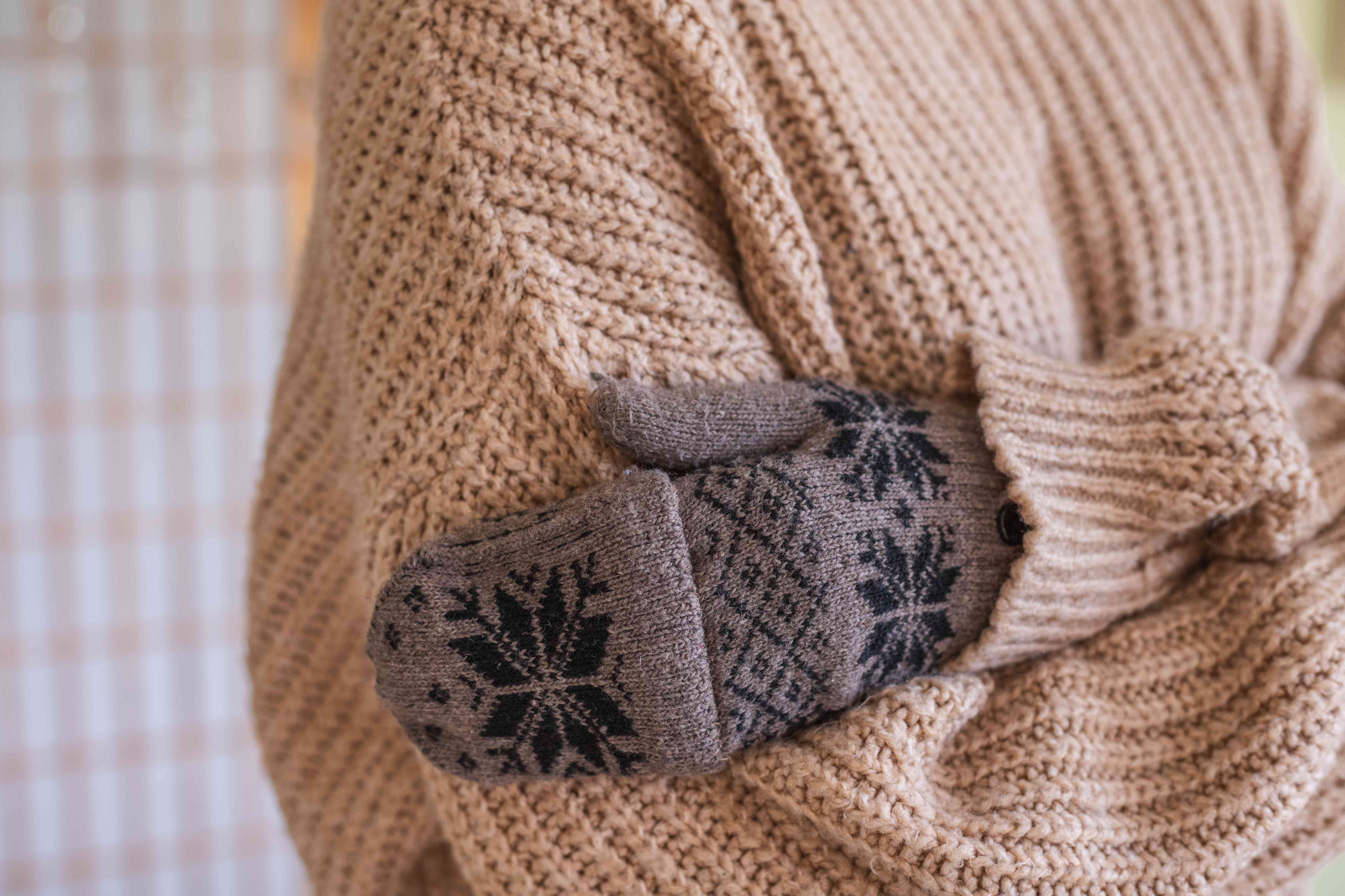 person wearing chunky tan sweater hugs self while wearing sweater patterned mittens