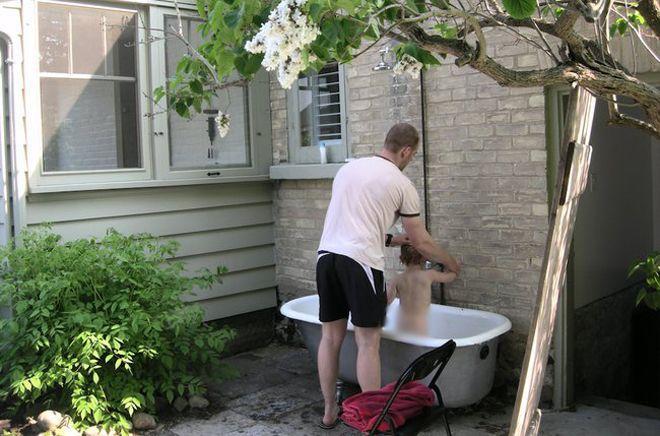 Man bathing a toddler in an outdoor bathtub