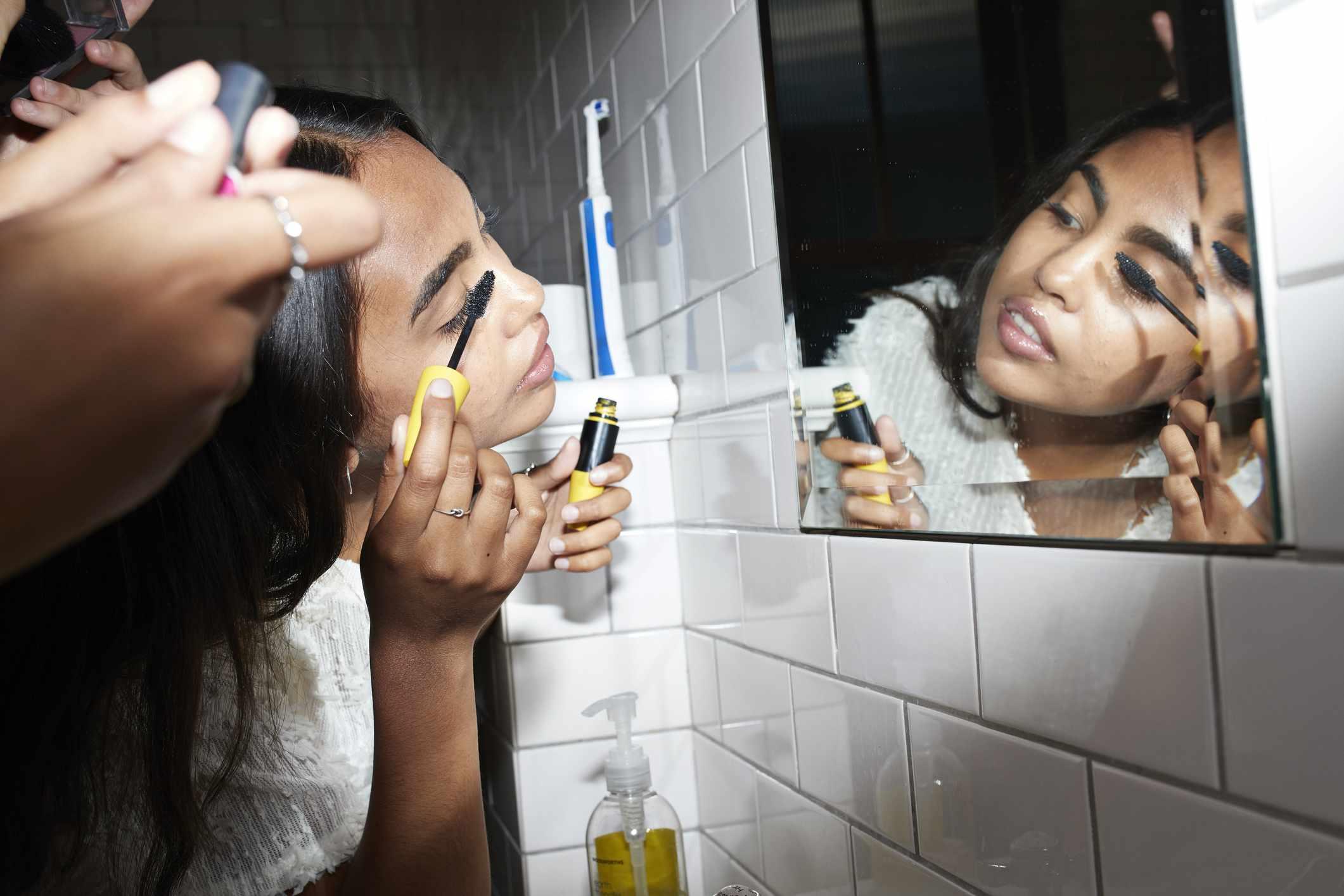 A young Asian woman applies mascara in the mirror.