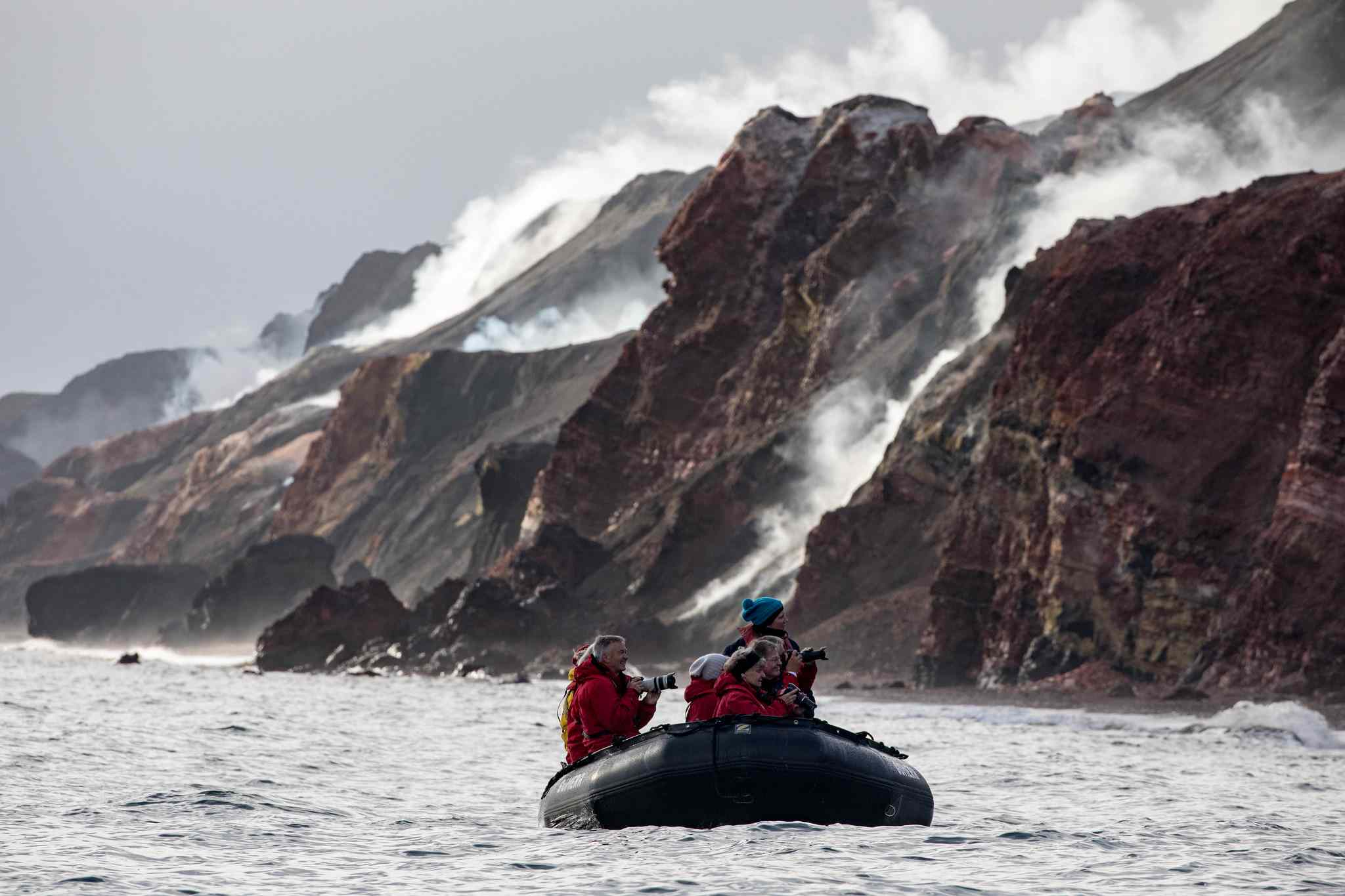 People photographing the smoking hills from a boat