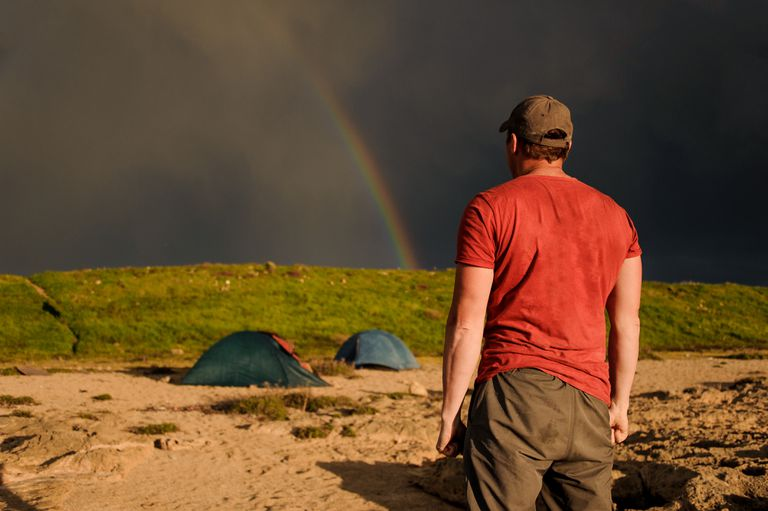 Man standing and looking on the rainbow in the dark sky