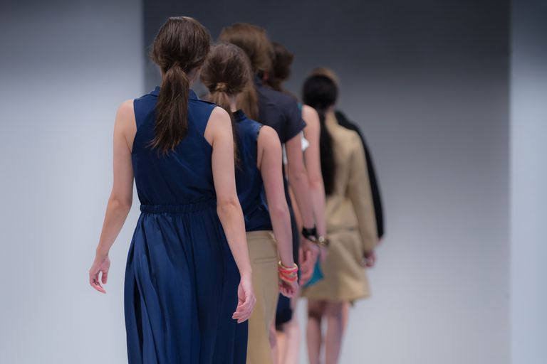 Rear view of models walking down a fashion runway