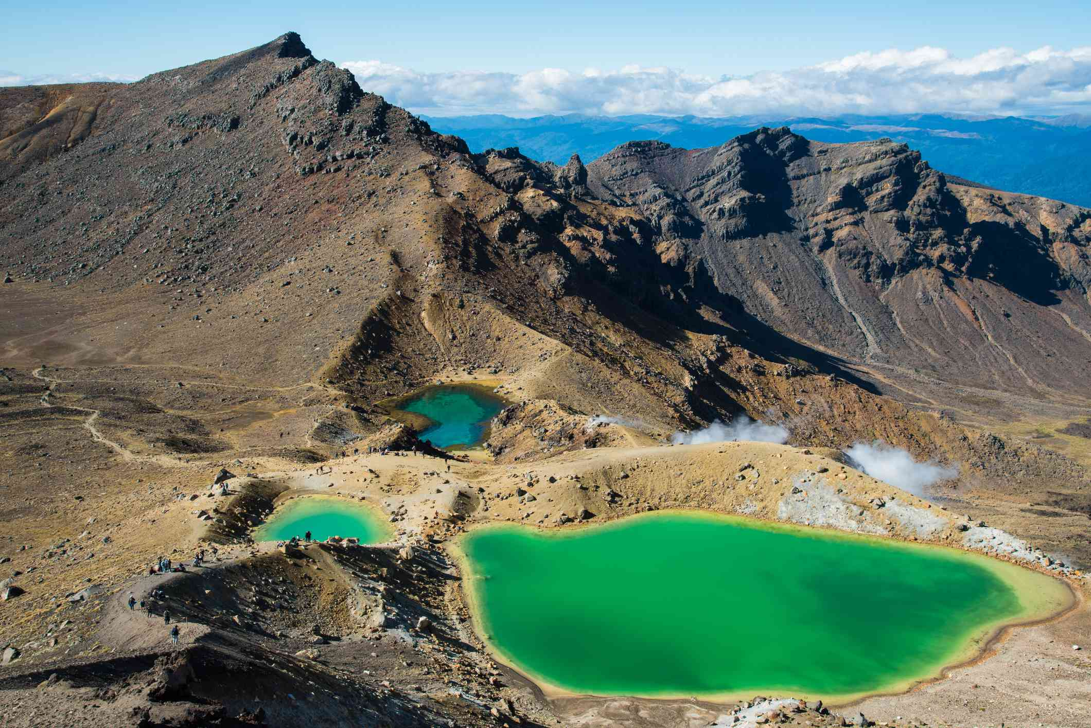one large and two smaller emerald green lakes surrounded by mountains with a bright blue sea of water, blue sky, and low, white clouds in the distance at Tongariro Alpine Crossing