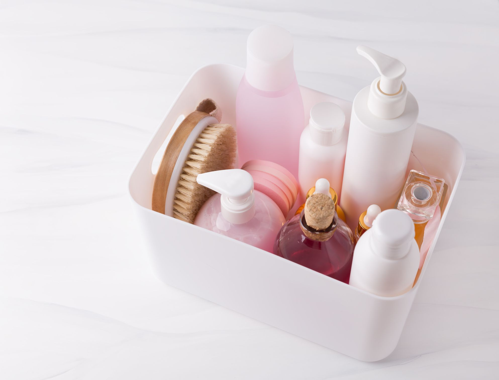 Parred down pink and white beauty and skincare products in a plastic organizer.