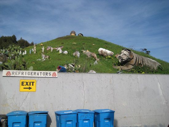 Large statues on a hillside with blue bins below.