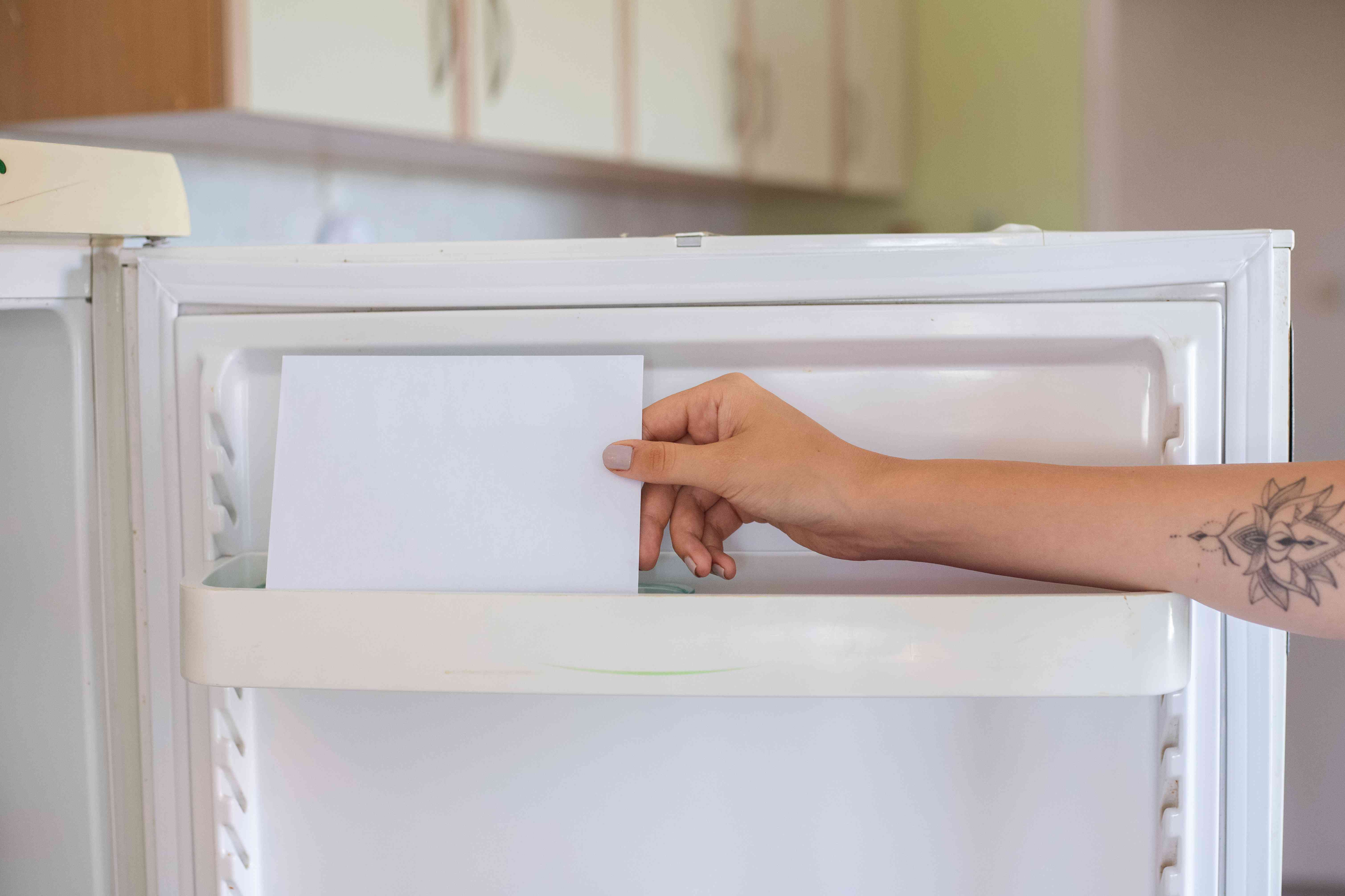 tattooed hand places dried tomato seeds in white envelope in kitchen freezer