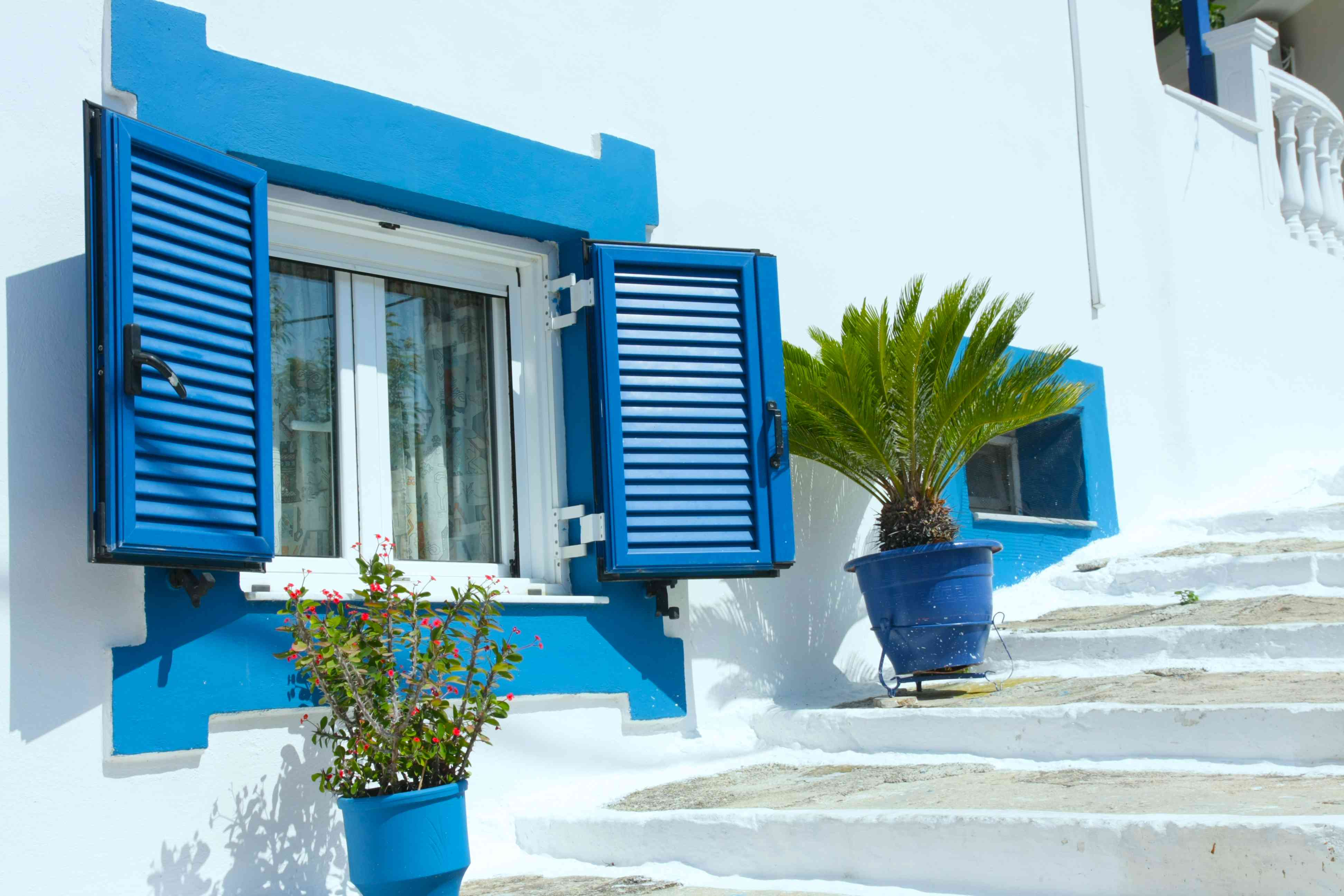 White building with blue shutters on a square window