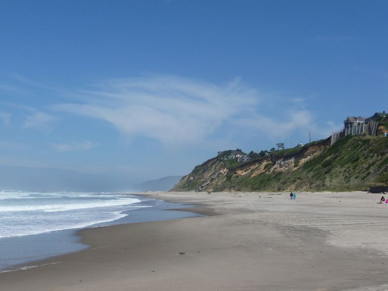 A sandy beach meets the Pacific Ocean on a hilly coastline under blue skies