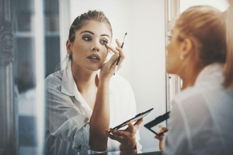 woman puts on makeup