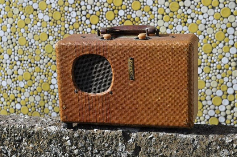 An antique portable radio with bluetooth speaker