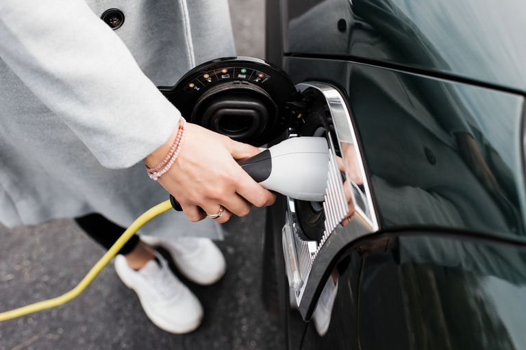 woman's hand plugging in a charging lead to her electric car