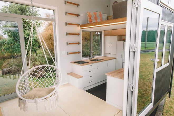 Main room with hanging chair and the kitchen off to the side