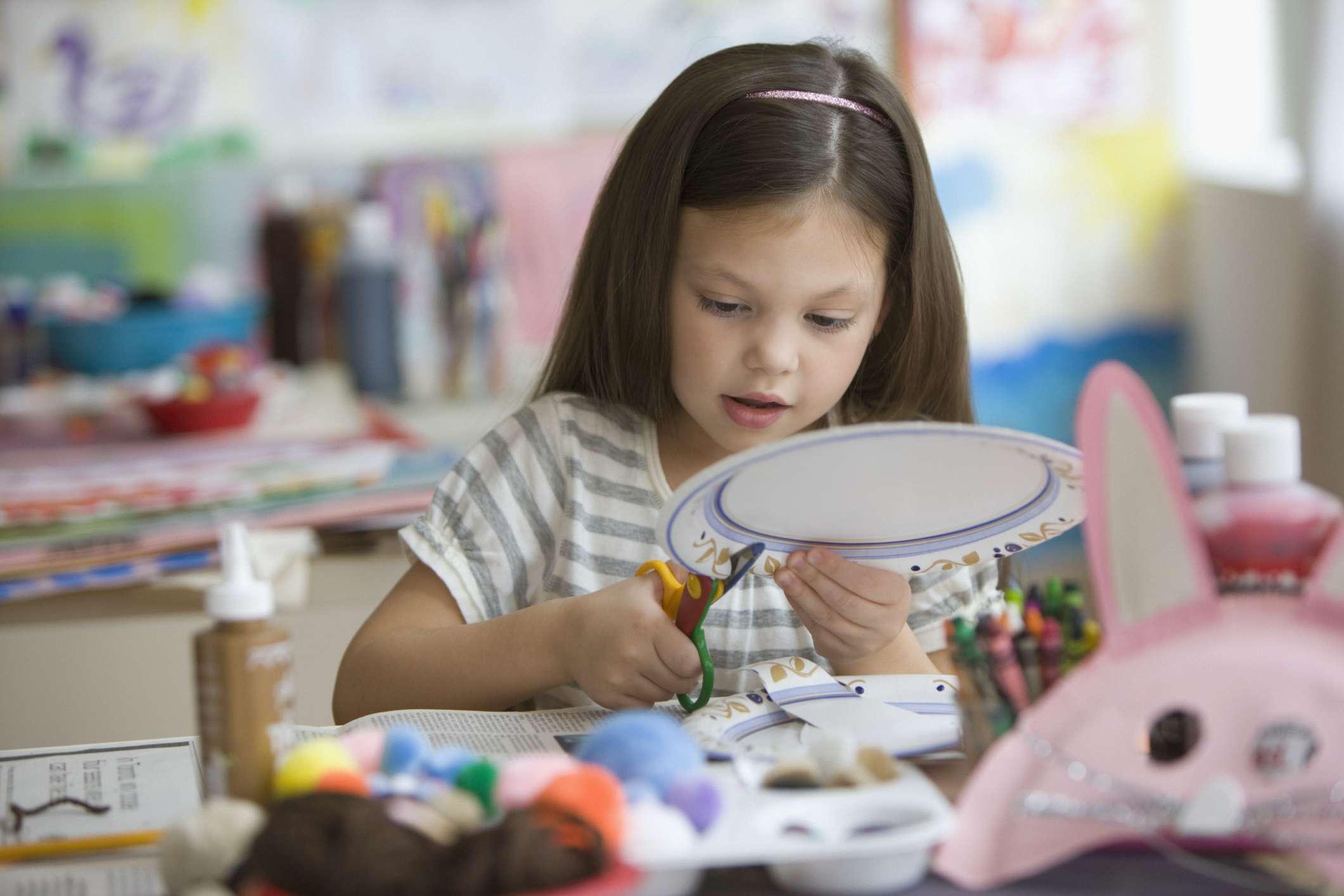 Caucasian girl cutting paper plate with scissors