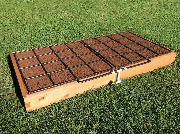 Rectangular garden bed with black grid over dirt, sitting on grass