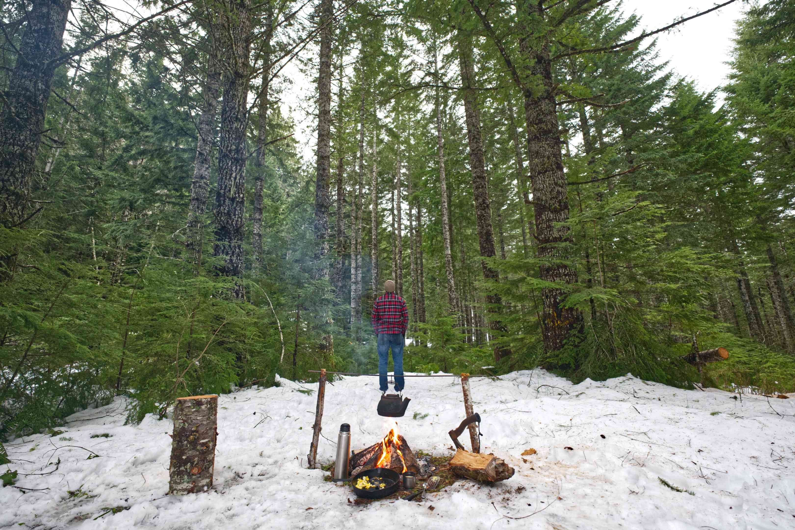 person camping in snowy woods with trees and campfire