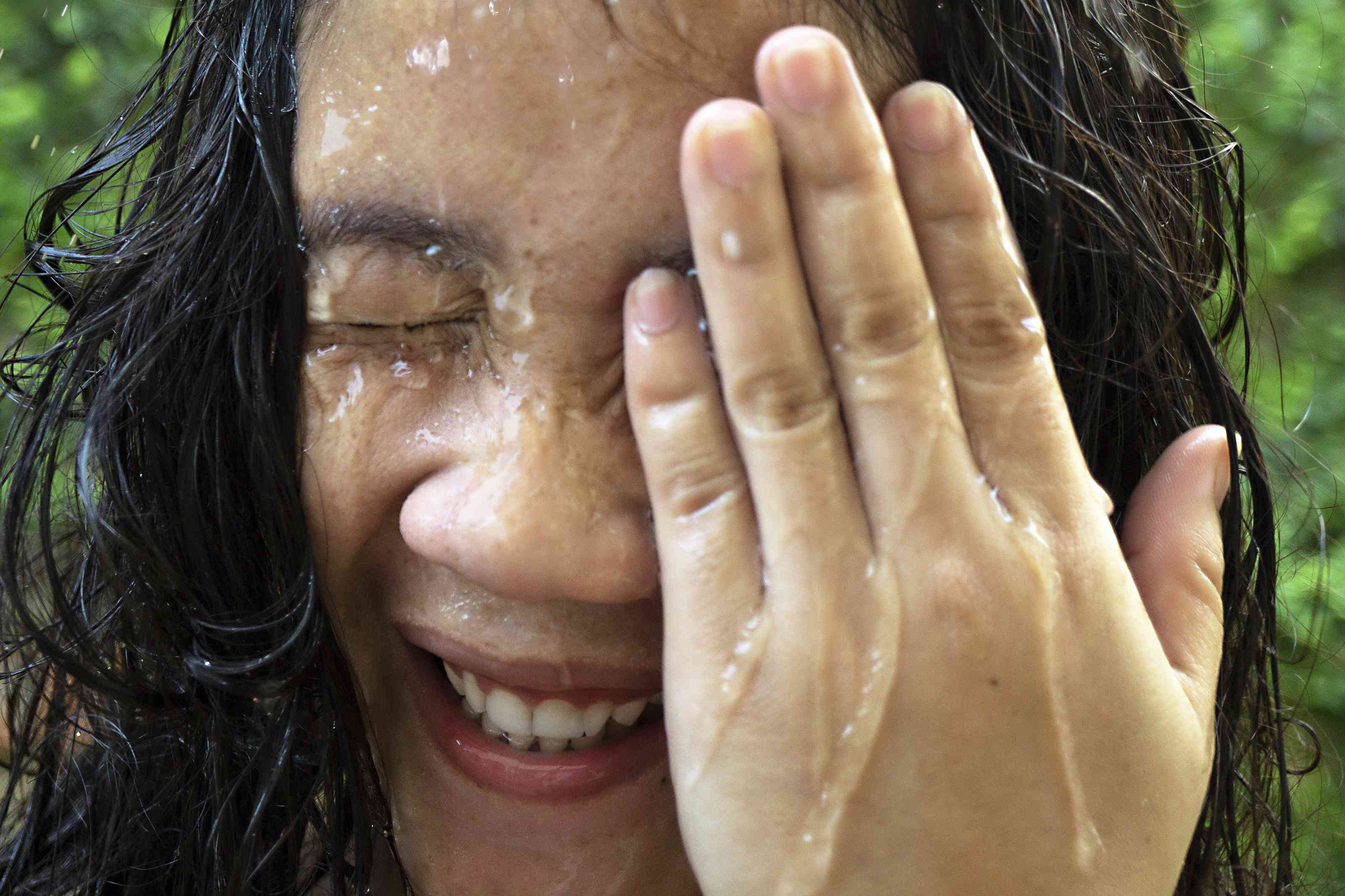 woman splashes water on face