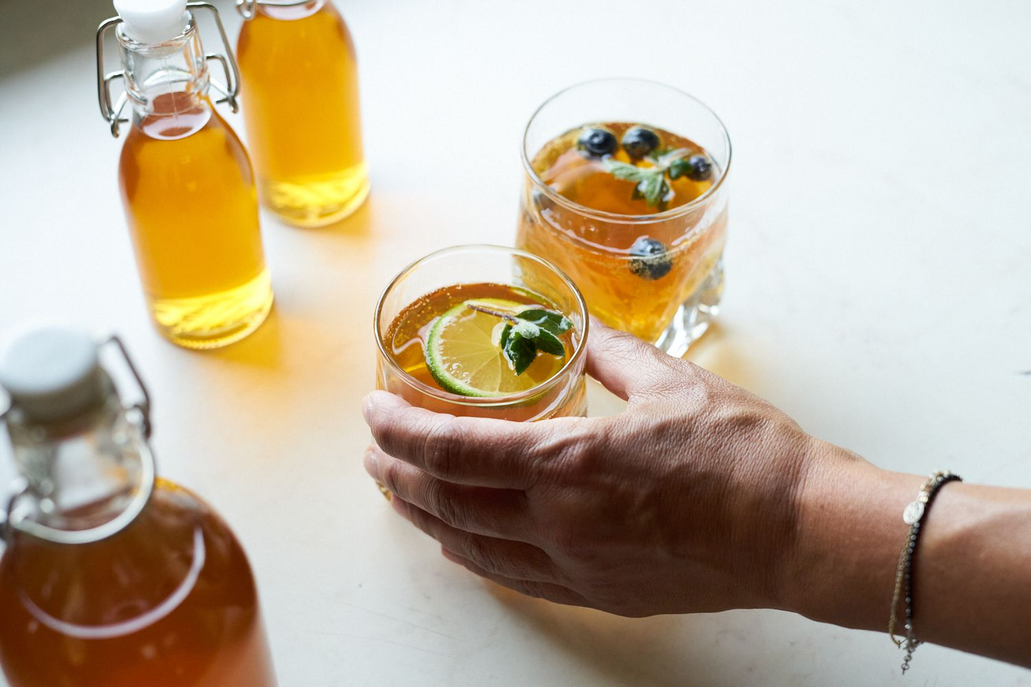 hand reaches for glass of homemade kombucha with lime and berries next to sealed bottles