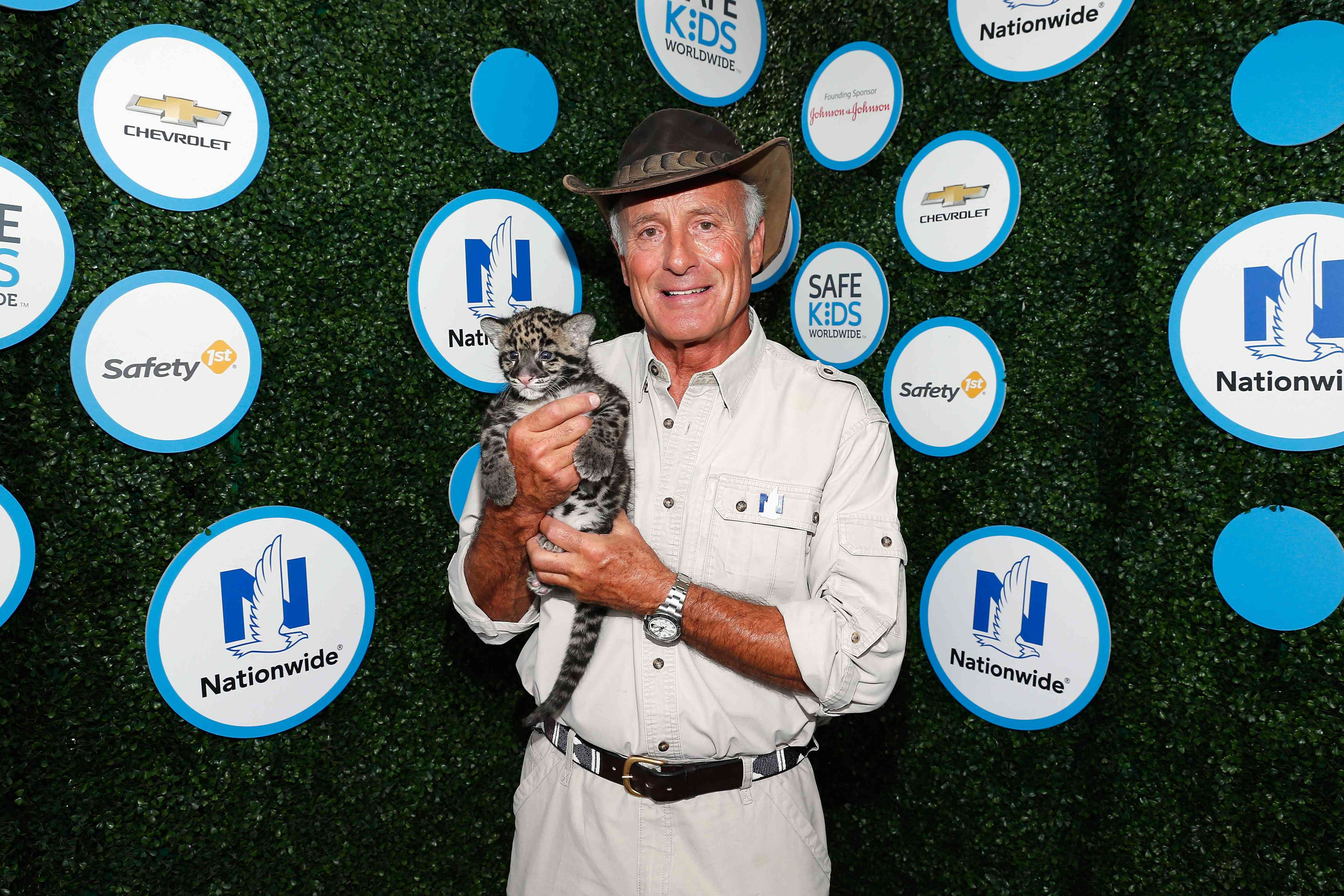 Jack Hanna posing with a big cat cub